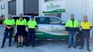 Staff of MG Roberts Plumbing pose outside their office with company branded ute behind
